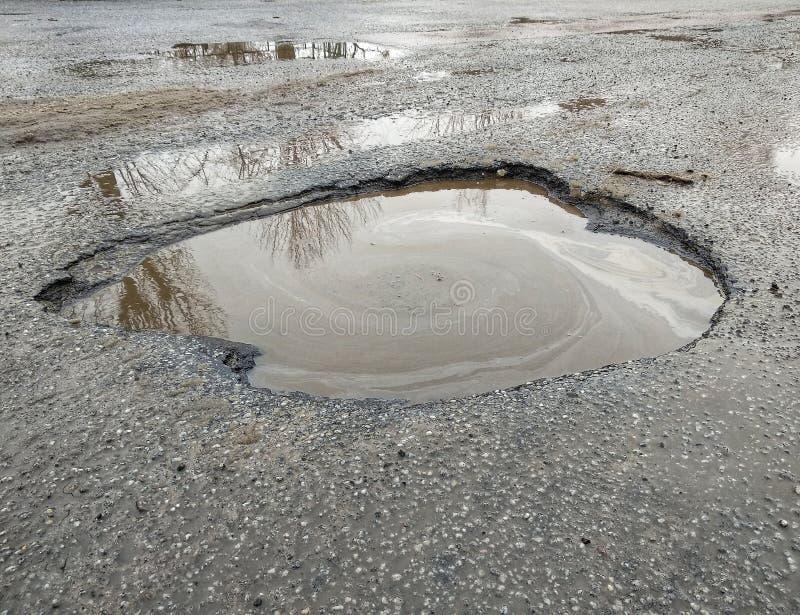 O grande poço encheu-se com água na coberta do asfalto, estrada quebrada, reflexão do ambiente na água, estradas ucranianas fotografia de stock royalty free