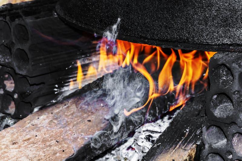 O grande potenciômetro de cozimento preto em um fogão rústico improvisou no floo imagens de stock royalty free