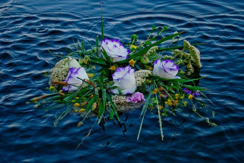 O grande ramalhete bonito das flores envolve a flutuação no rio nas ondas na água de Ivan Kupala imagens de stock