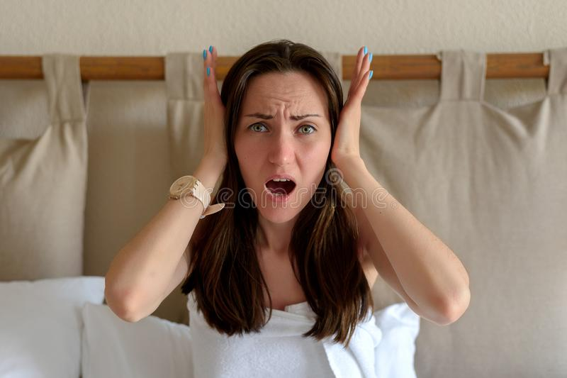 O grande retrato de uma mulher que guarda sua cabeça com suas mãos, o conceito da dor de cabeça, enxaqueca, vizinhos ruidosos, co imagem de stock
