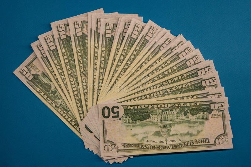 O grande rolo gordo do dinheiro isolou-se em um fundo azul fotografia de stock