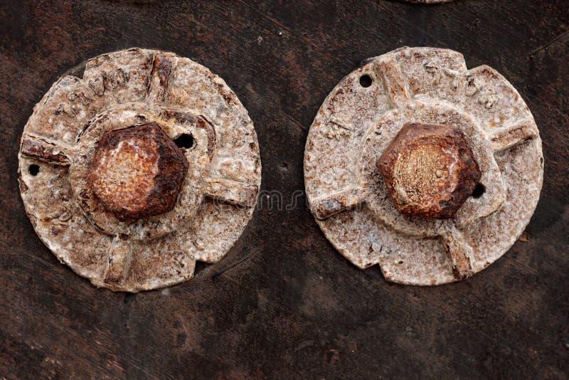 O grande vintage dois velho pesado oxidou os parafusos em uma parede de madeira resistida, textura do fundo do grunge imagens de stock royalty free