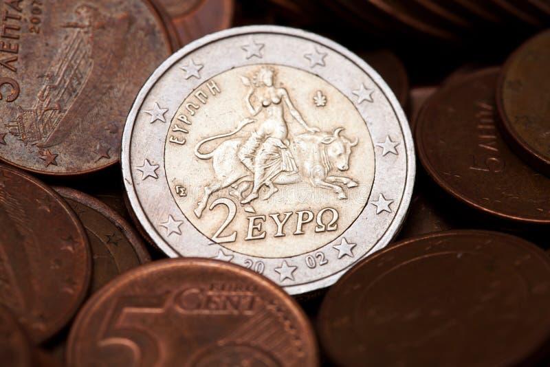 O grego dois euro inventa entre moedas de cinco centavos imagem de stock royalty free