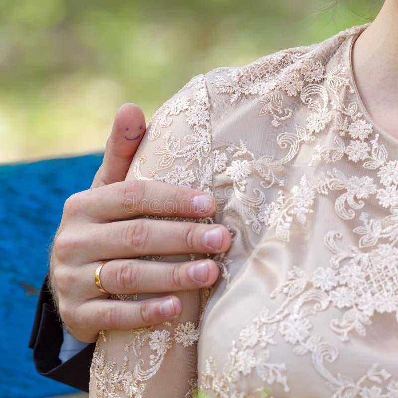 O groom& x27; mão de s com um anel no bride& x27; ombro de s Um par mim fotografia de stock royalty free