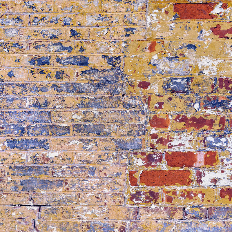 O Grunge resistiu ao vermelho da parede de tijolo com o peeli amarelo e branco azul fotos de stock royalty free