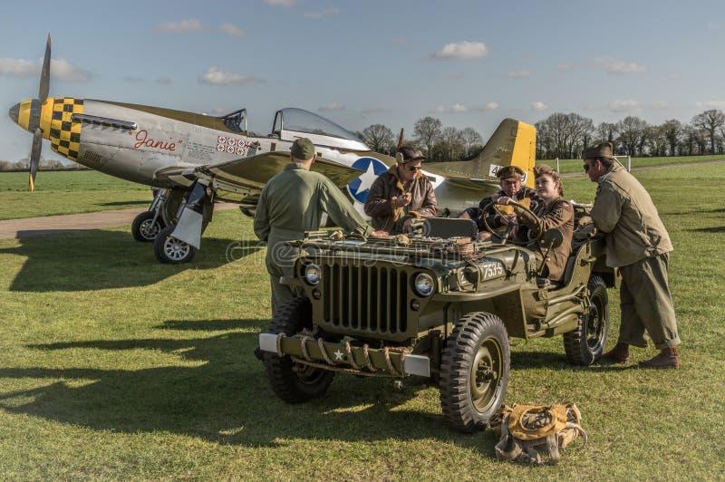 O grupo à terra senta-se em um jipe WW2 com um mustang P-51 no backgro imagens de stock royalty free