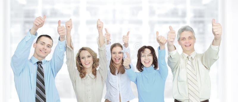 O grupo bem sucedido de homens de negócios levanta suas mãos no escritório fotografia de stock royalty free