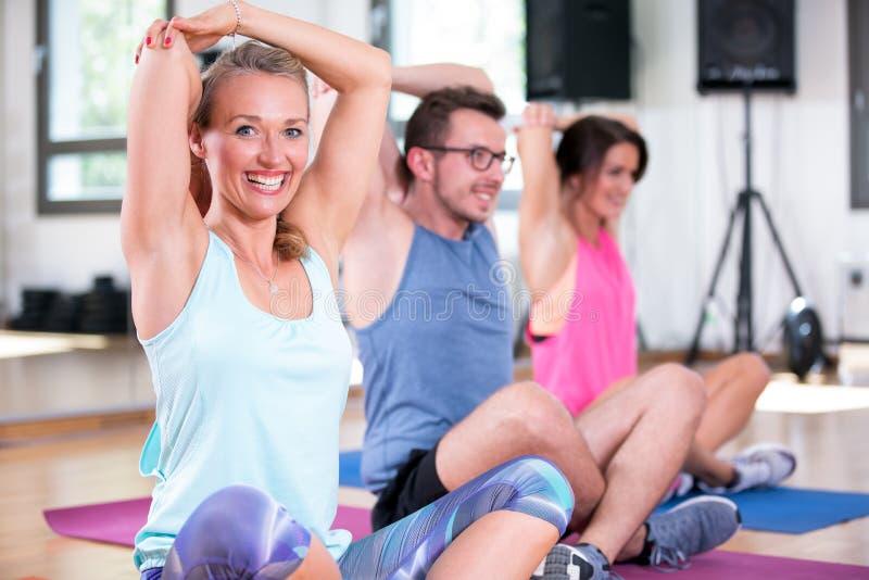 O grupo bonito do homem das mulheres está fazendo o exercício da aptidão do esporte em um gym foto de stock royalty free