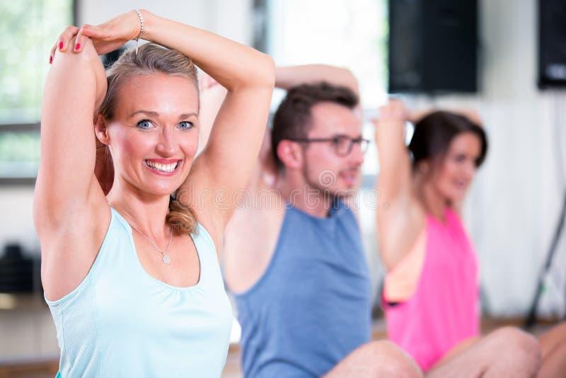 O grupo bonito do homem das mulheres está fazendo o exercício da aptidão do esporte em um gym fotografia de stock