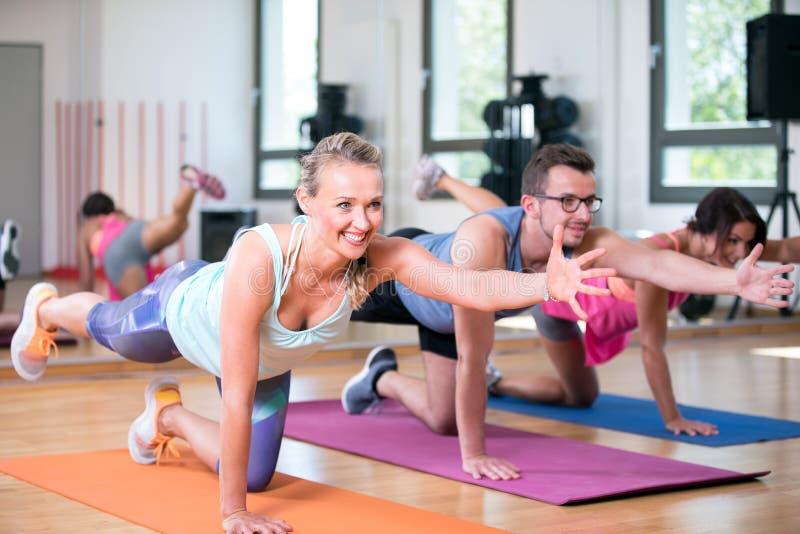 O grupo bonito do homem das mulheres está fazendo o exercício da aptidão do esporte em um gym imagem de stock