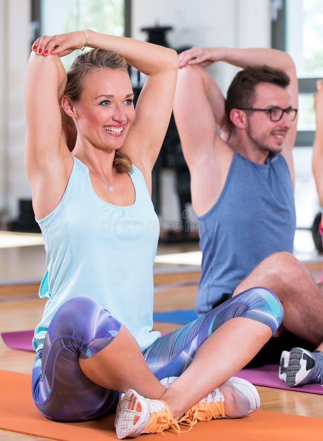 O grupo bonito do homem das mulheres está fazendo o exercício da aptidão do esporte em um gym fotos de stock royalty free