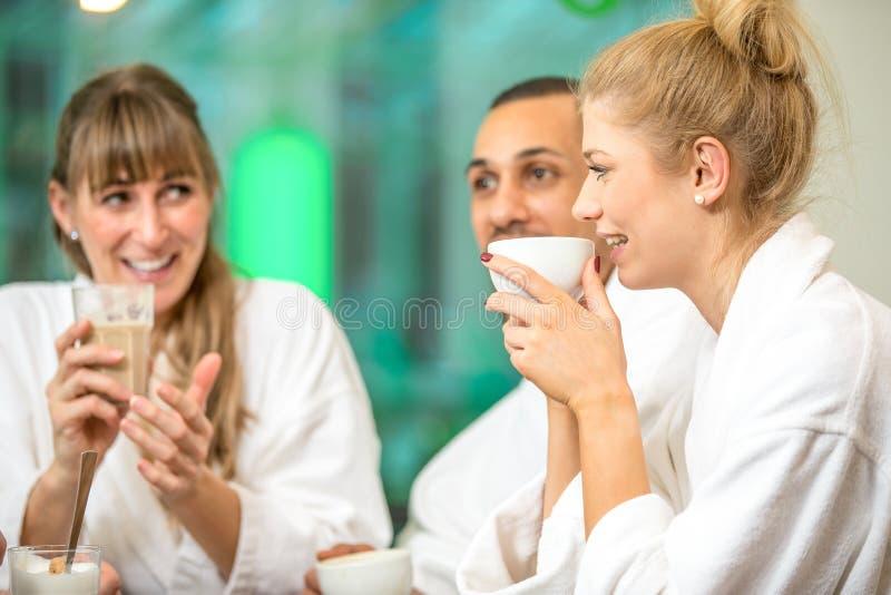 O grupo bonito novo est? fazendo o bem-estar com caf? e um champanhe fotos de stock royalty free