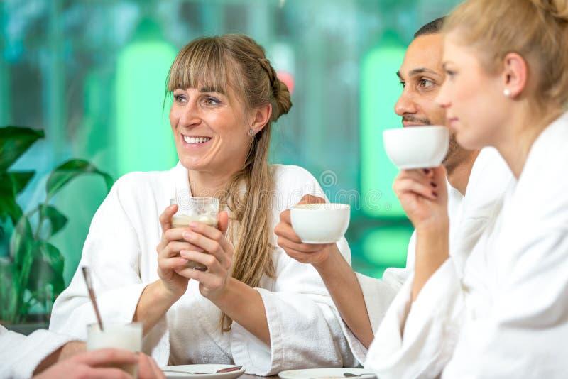 O grupo bonito novo est? fazendo o bem-estar com caf? e um champanhe imagens de stock royalty free
