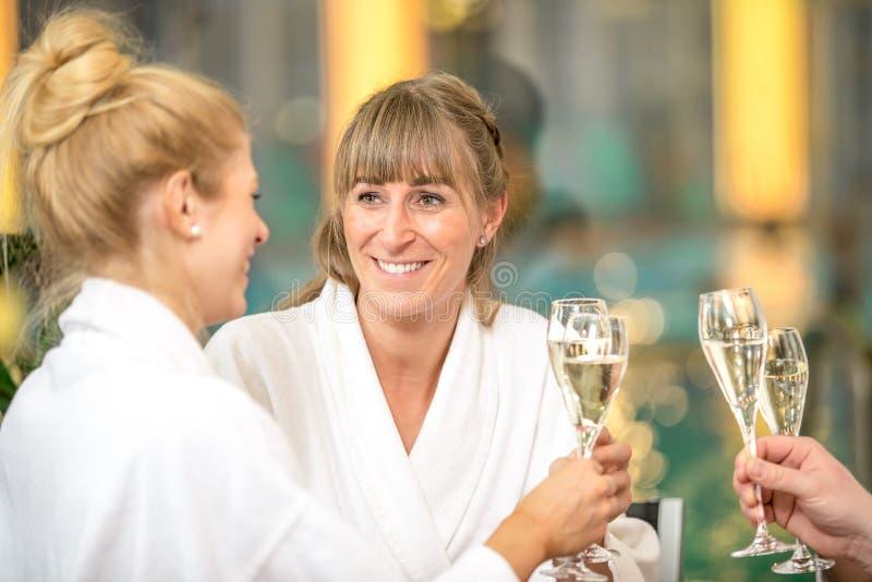 O grupo bonito novo est? fazendo o bem-estar com caf? e um champanhe imagem de stock royalty free