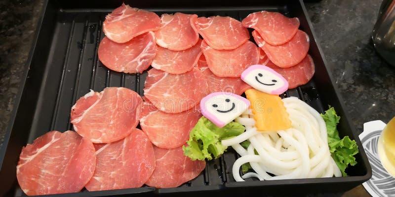 O grupo da matéria prima da carne de porco tem os peixes, o udon, a cenoura e a alface na cor plástica do preto da placa, aliment foto de stock