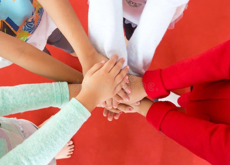 O grupo da menina uniu suas mãos em um círculo Sinal da vitória fotografia de stock