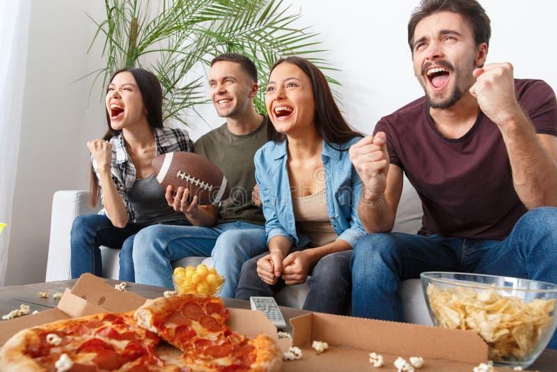 O grupo de aficionados desportivos dos amigos que olha o rugby combina a vitória imagem de stock royalty free