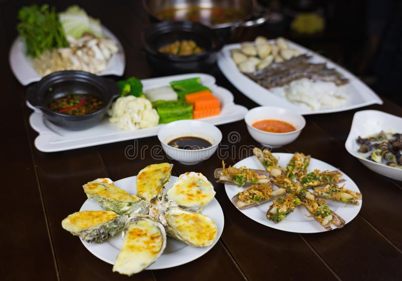 O grupo de alimento de mar de Ásia com escargot do coco, navalha do assado, ostra grelhada queijo, ferveu o vegetal que come com  fotos de stock