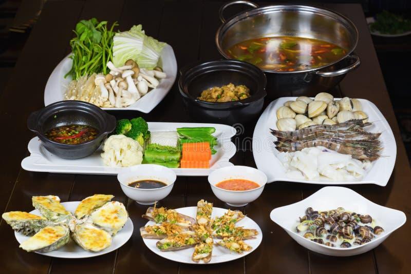 O grupo de alimento de mar de Ásia com escargot do coco, navalha do assado, ostra grelhada queijo, ferveu o vegetal que come com  imagem de stock royalty free