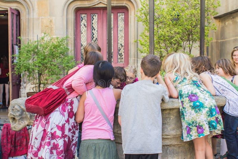 O grupo de alunos franceses espreita para baixo no bem no dianteiro fotos de stock royalty free