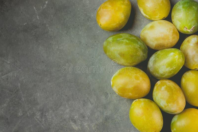 O grupo de ameixas amarelas e verdes suculentas maduras dispersadas arranjou na beira no fundo de pedra escuro Colheita da queda  imagem de stock royalty free