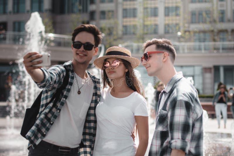 O grupo de amigos est? fazendo um ar livre de Selfie A fonte est? no fundo imagem de stock