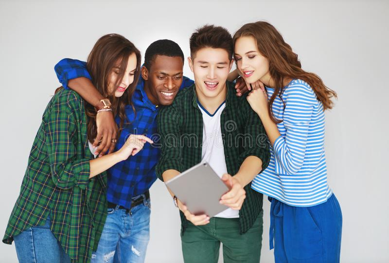O grupo de amigos felizes dos povos dos estudantes com os dispositivos das tabuletas dos telefones ri imagens de stock royalty free