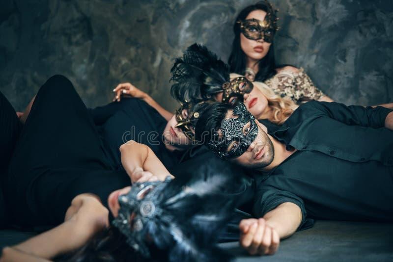 O grupo de amigos na máscara do carnaval do disfarce que senta-se no assoalho relaxa após o partido imagens de stock royalty free