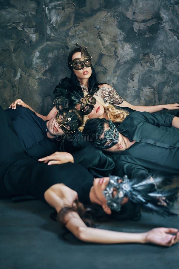 O grupo de amigos na máscara do carnaval do disfarce que senta-se no assoalho relaxa após o partido foto de stock
