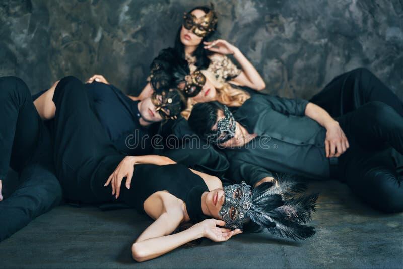 O grupo de amigos na máscara do carnaval do disfarce que senta-se no assoalho relaxa após o partido fotos de stock royalty free