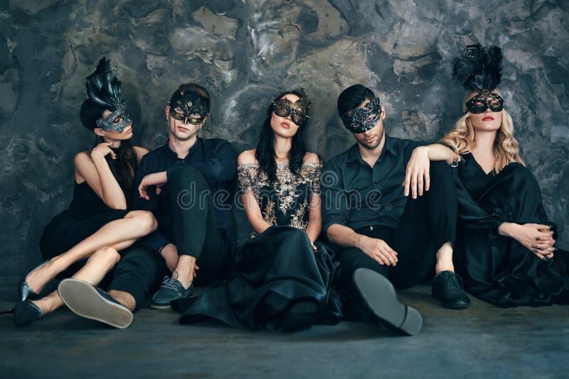 O grupo de amigos na máscara do carnaval do disfarce que senta-se no assoalho relaxa após o partido imagem de stock