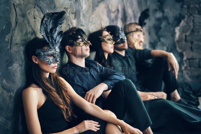 O grupo de amigos na máscara do carnaval do disfarce que senta-se no assoalho relaxa após o partido fotos de stock
