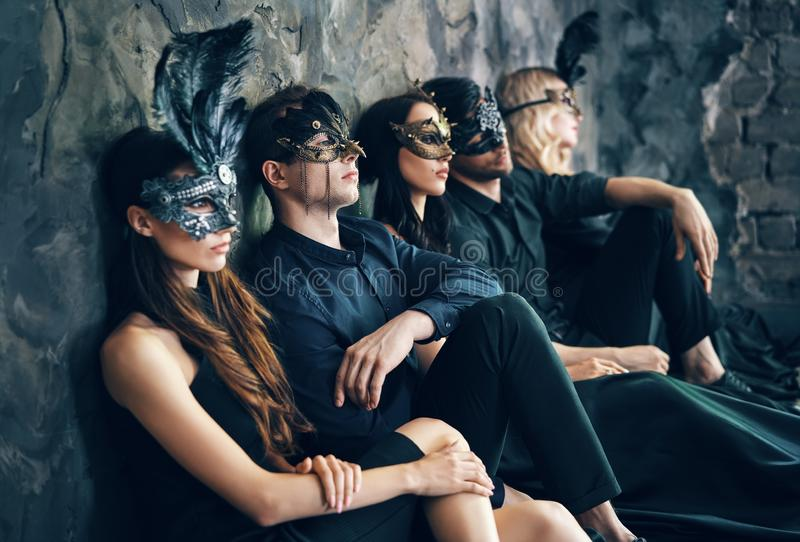 O grupo de amigos na máscara do carnaval do disfarce que senta-se no assoalho relaxa após o partido fotografia de stock royalty free