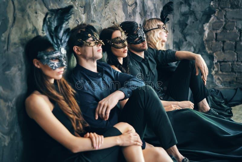 O grupo de amigos na máscara do carnaval do disfarce que senta-se no assoalho relaxa após o partido fotografia de stock