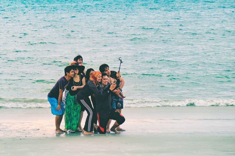 O grupo de amigos novos faz selfies na praia fotos de stock royalty free