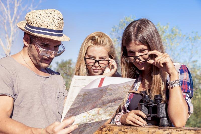 O grupo de caminhantes novos procura no mapa imagem de stock royalty free