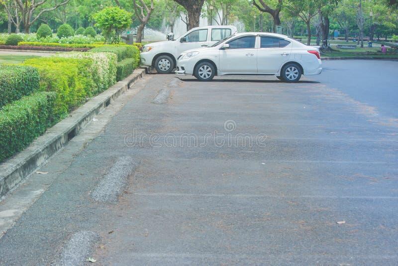 O grupo de carros estacionou no assoalho concreto no parque de estacionamento do carro cercado com natural verde foto de stock
