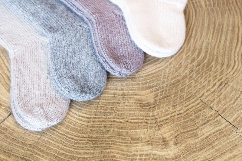 O grupo de caxemira colorida diferente pequena bonito fez malha peúgas recém-nascidas do bebê em um fundo de madeira da mesa imagem de stock