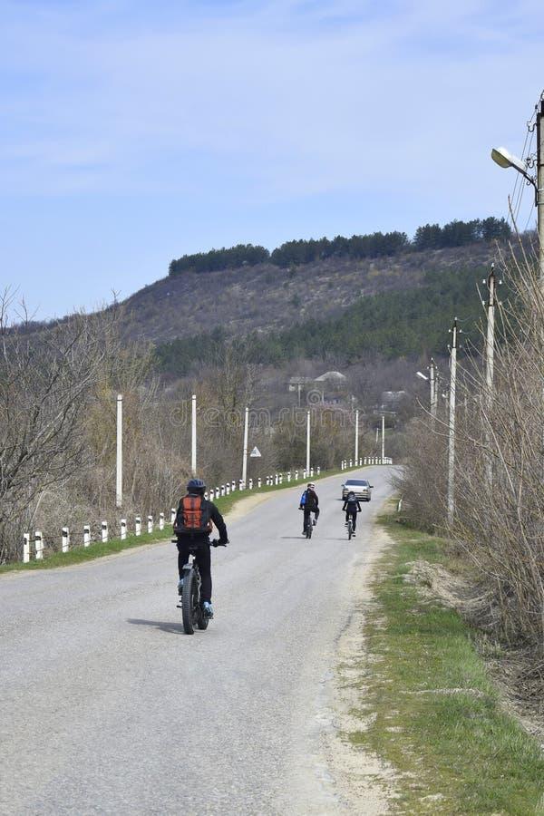 O grupo de ciclistas novos est? conduzindo ao longo de uma estrada asfaltada imagem de stock