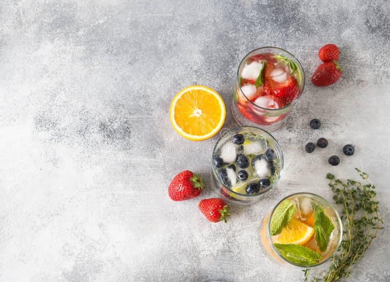 O grupo de cocktail saudáveis do verão, vário citrino infundiu águas, limonadas ou mojitos, com o cal e os mirtilos, a laranja e  fotografia de stock royalty free