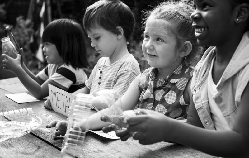 O grupo de colegas das crianças que aprendem a biologia recicla o ambiente fotos de stock