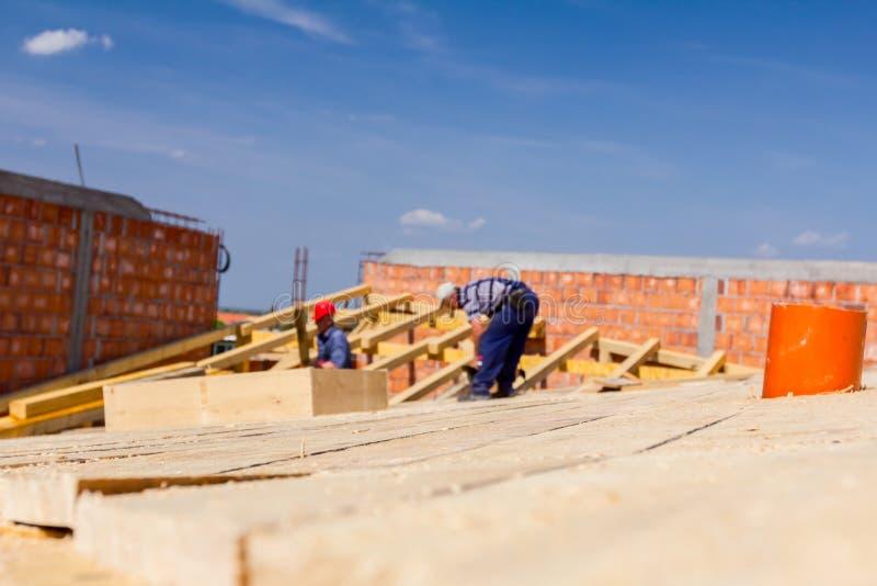 O grupo de construção dos carpinteiros está trabalhando no telhado novo fotografia de stock