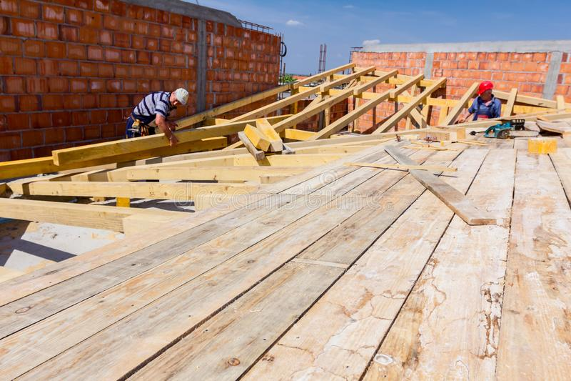 O grupo de construção dos carpinteiros está trabalhando no telhado novo foto de stock