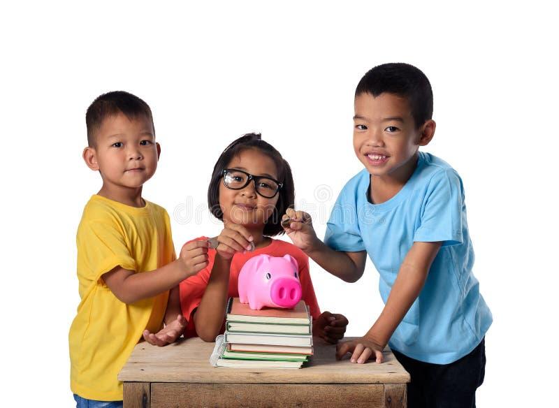 O grupo de crianças asiáticas tem o divertimento com o mealheiro isolado no fundo branco foto de stock royalty free