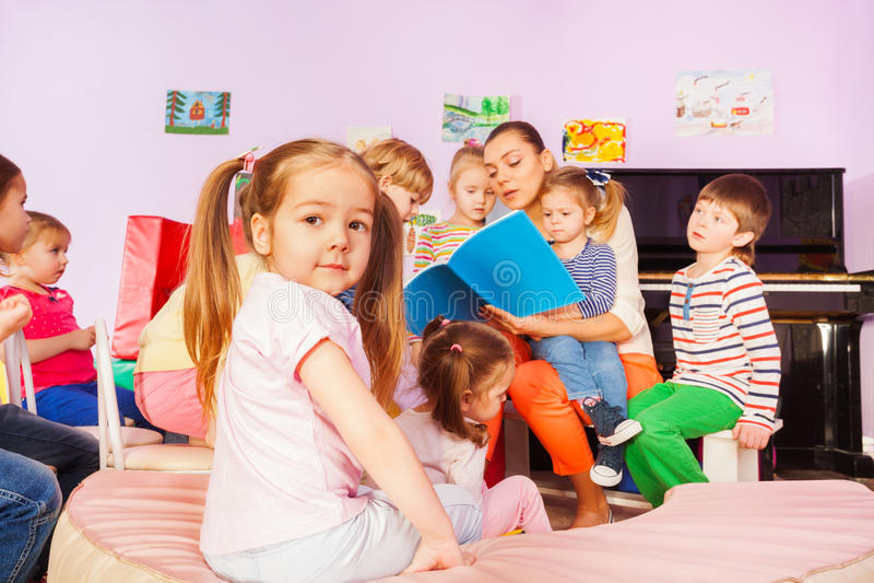O grupo de crianças escuta o livro de leitura do professor imagem de stock