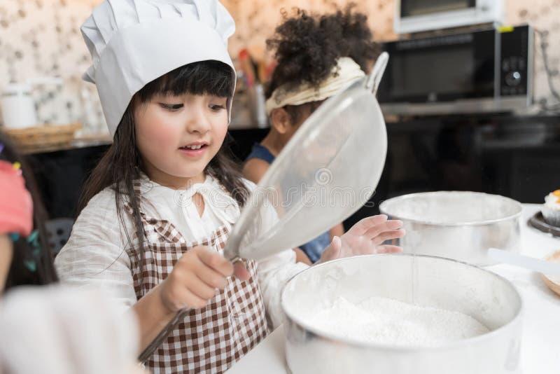 O grupo de crianças está preparando a padaria na cozinha Crianças que aprendem a cozinhar cookies fotos de stock royalty free