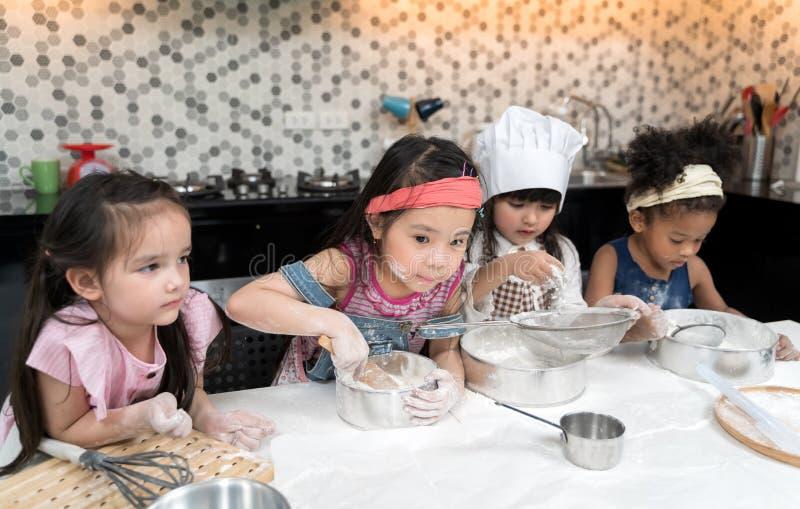 O grupo de crianças está preparando a padaria na cozinha Crianças que aprendem a cozinhar cookies fotografia de stock