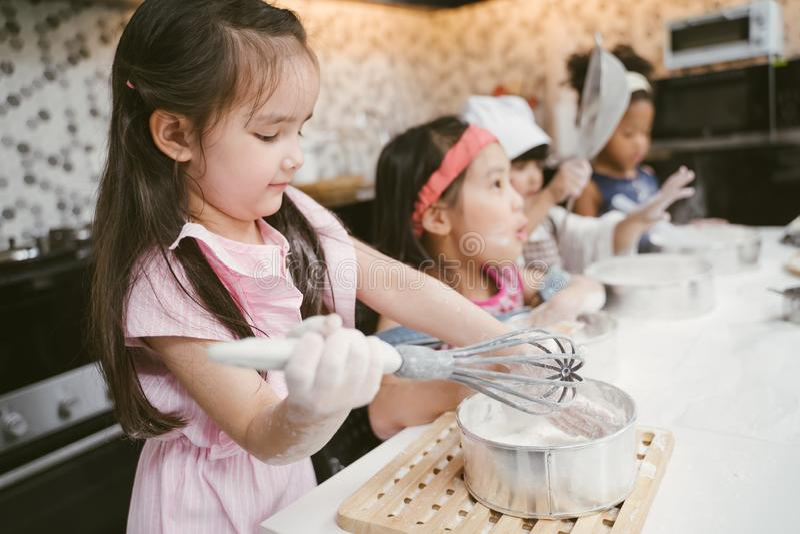 O grupo de crianças está preparando a padaria na cozinha Crianças que aprendem a cozinhar cookies imagens de stock royalty free