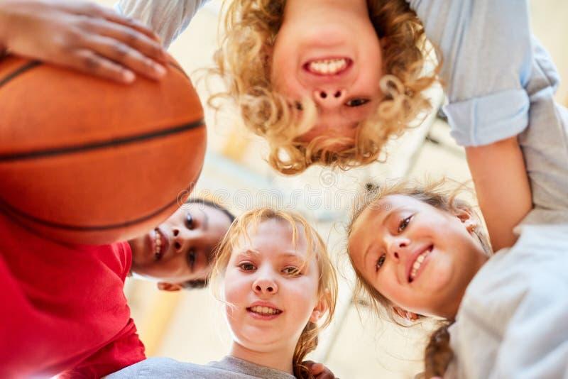 O grupo de crianças forma uma equipe de basquetebol fotos de stock royalty free