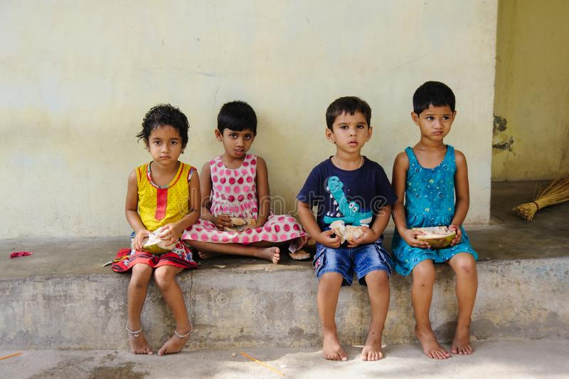 O grupo de crianças indianas senta-se na rua e em comer cocos o 11 de fevereiro de 2018 Puttaparthi, Índia fotografia de stock royalty free